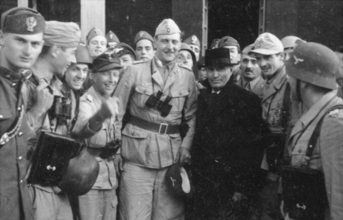 Benito Mussolini (w czarnym płaszczu) zeswoimi niemieckimi wybawcami. Wśrodku zlornetką Otto Skorzeny