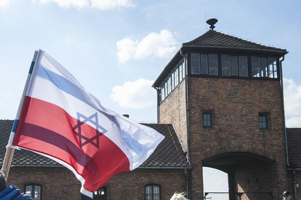 Flagi Polski i Izraela przed bramą do niemieckiego obozu koncentracyjnego Auschwitz