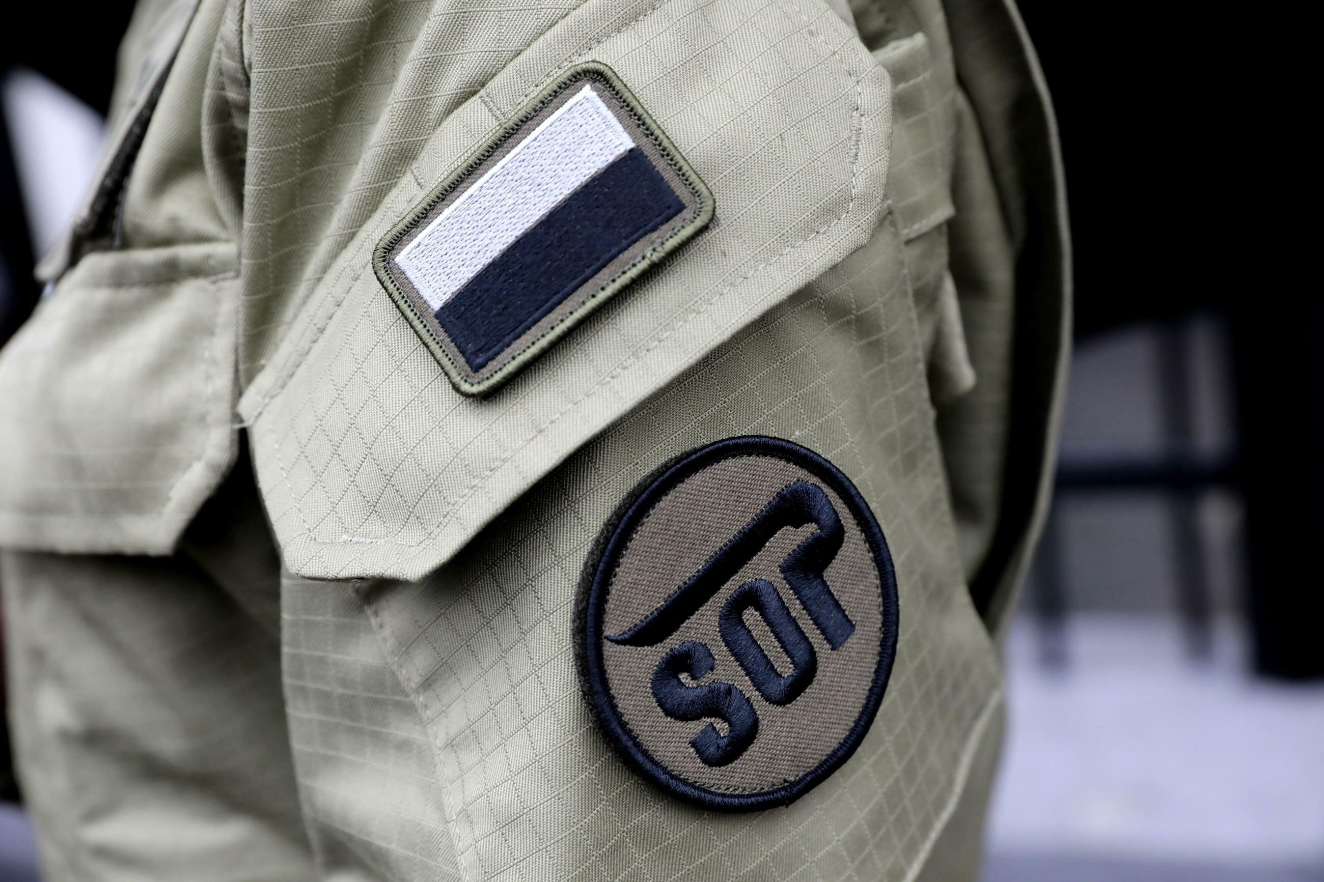 Funkcjonariusz i logo Służby Ochrony Państwa