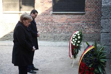 Kanclerz Niemiec Angela Merkel (L) oraz premier Mateusz Morawiecki (P) składają kwiaty przy Ścianie Straceń na terenie byłego niemieckiego nazistowskiego obozu zagłady Auschwitz.
