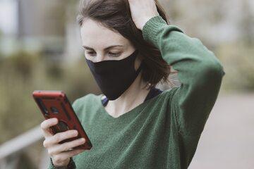 kobieta w maseczce z telefonem, zdjęcie ilustracyjne