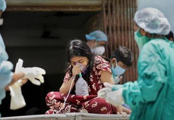 Kolkata, Indie. Pracownicy służby zdrowia zajmuję się pacjentem z podejrzeniem zakażenia koronawirusem