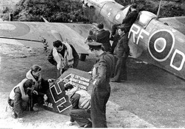 """Lotnicy polskiego dywizjonu myśliwskiego 303 oglądają szczątki zestrzelonego samolotu niemieckiego """"Ju 88"""". Z prawej widoczny samolot """"Spitfire"""" należący do pilota Jana Zumbacha"""