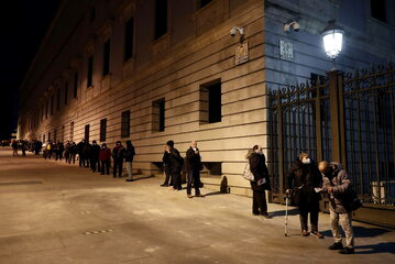 Madryt. Kolejka ludzi czekających na uzyskanie paczek z żywnością.