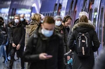 Pasażerowie w maskach wchodzą do pociągu w Szwecji, zdjęcie ilustracyjne