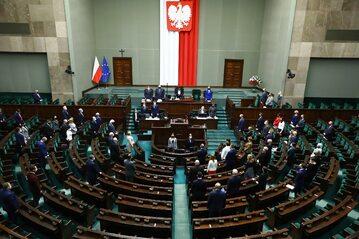 Posłowie na sali obrad, stoją w minucie ciszy dla Jana Lityńskiego.