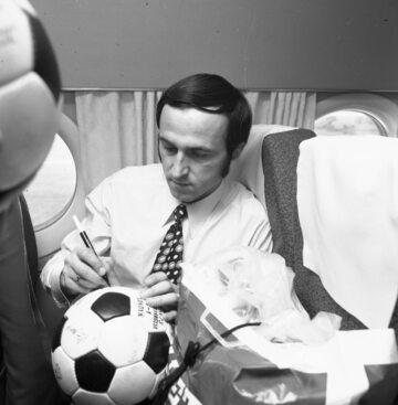 Powrót piłkarzy reprezentacji Polski po remisie z Anglią w 1973 r. Jan Domarski składa autografy na piłkach