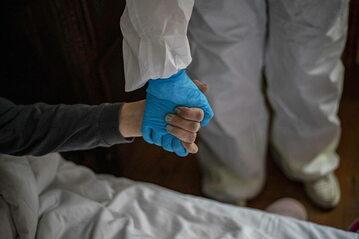 Pracownik służby zdrowia ubrany w ubrania ochronne pomaga chorej osobie, zdjęcie ilustracyjne