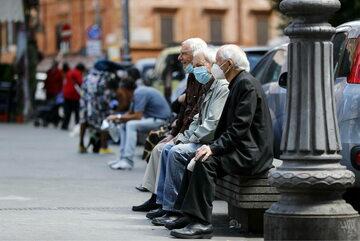Starsi panowie w maseczkach ochronnych siedzący na ławce w Rzymie, zdjęcie ilustracyjne