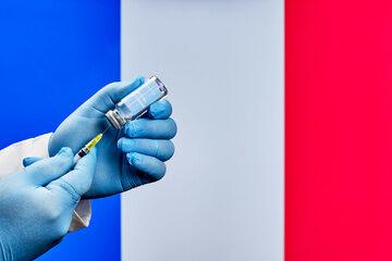 Szczepionka przeciw COVID-19 na tle francuskiej flagi, zdjęcie ilustracyjne