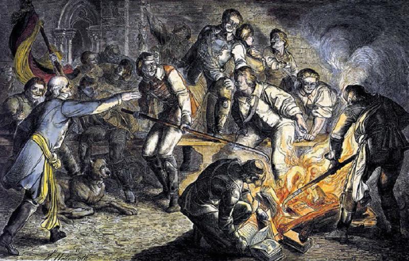 """Wartburg, 1817 r. Studenci ciskają w ogień książki autorów prohabsburskiej """"reakcji"""". Wzorują się na Lutrze, który rzucił w ogień upomnienie papieskie."""