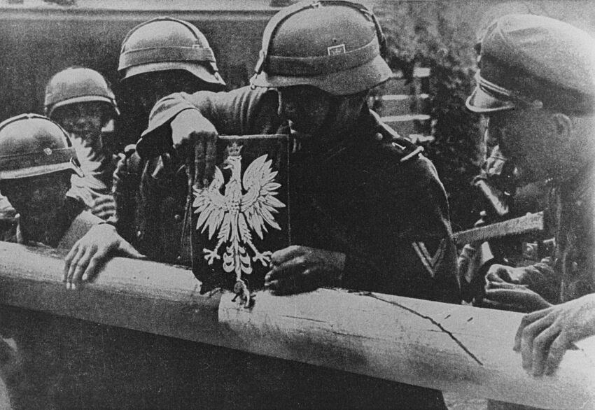 Wrzesień 1939 r. Żołnierze niemieccy niszczą szlaban graniczny i godło Polski