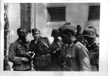 Żołnierze niemieccy z chusteczkami (jeden w masce przeciwgazowej) nad zwłokami ofiar NKWD we Lwowie