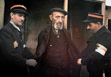 Żydowscy policjanci z Jüdischer Ordnungsdienst przeszukują mężczyznę, łódzkie getto, ok. 1942 r.